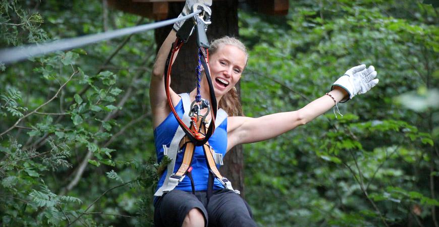 Junge Frau im Kletterwald München im Seilbahnelement